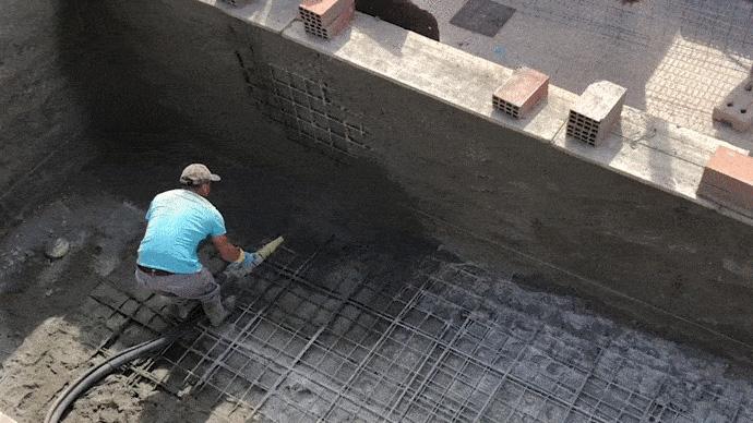 Obrero usando una gunitadora en una piscina