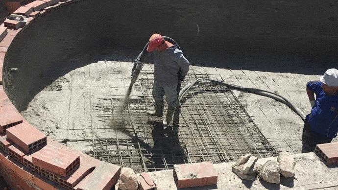 Obrero proyecta hormigon en suelo de piscina