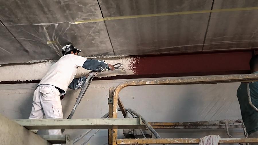 Un obrero proyecta mortero ignifugo en las vigas del techo