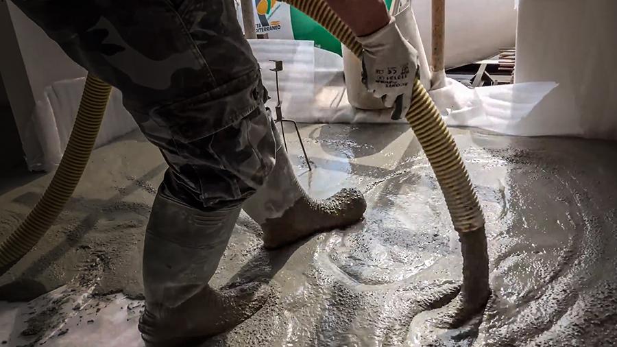 Obrero con botas de goma aplicando autonivelante