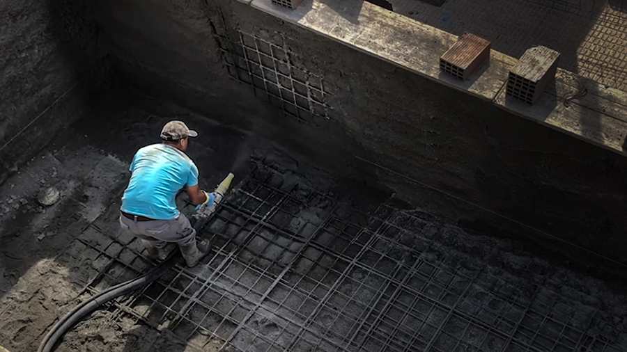 Trabajador usando una gunitadora en una piscina
