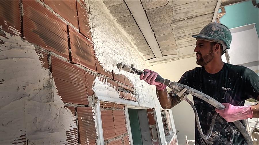 Trabajados proyectando mortero blanco en una fachada