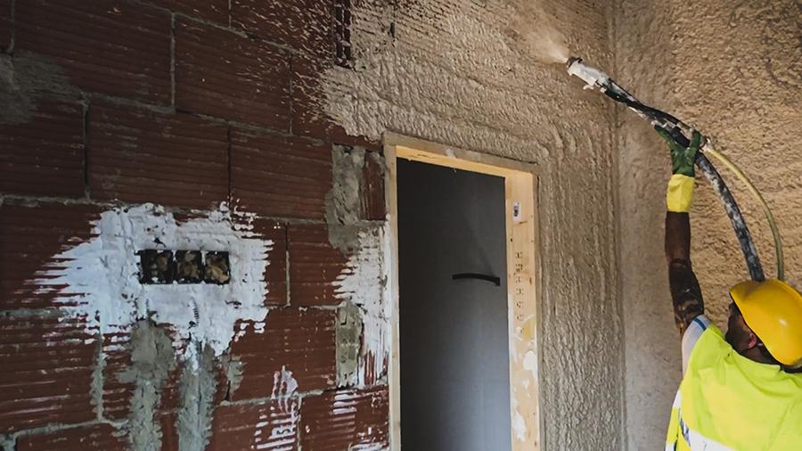 Obrero proyecta mortero en la zona de una puerta
