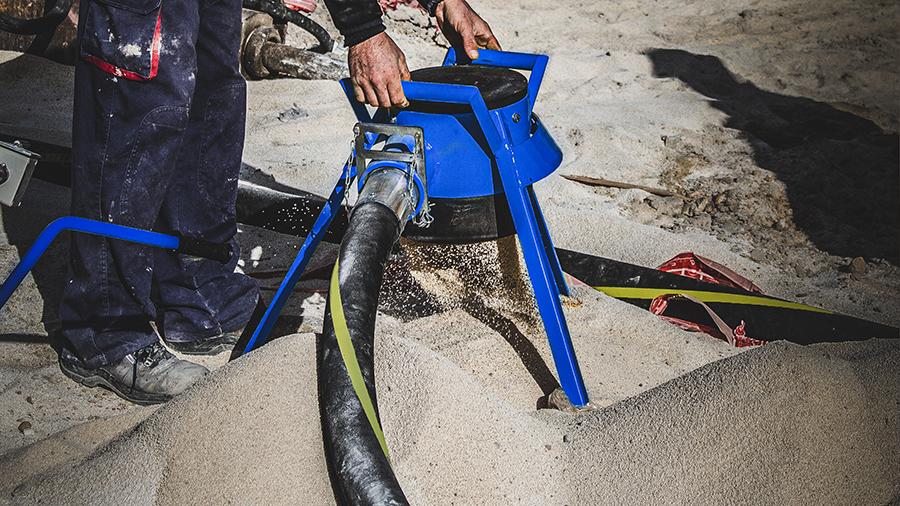 Operario sostiene un tripode que proyecta el material
